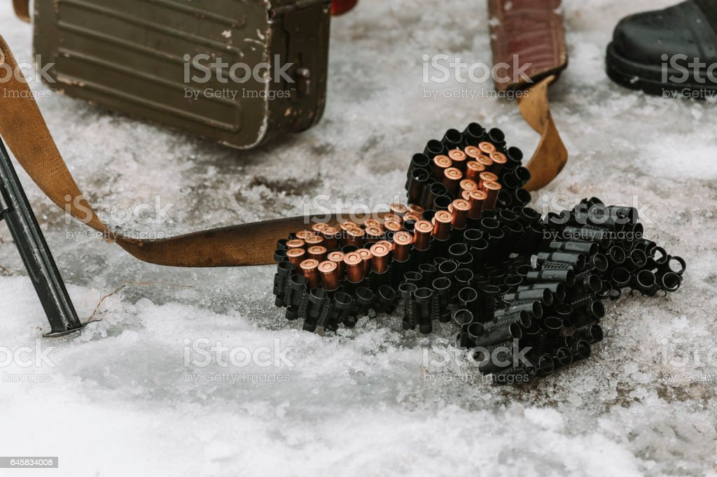 Ammunition belt with bullets lying on snow stock photo