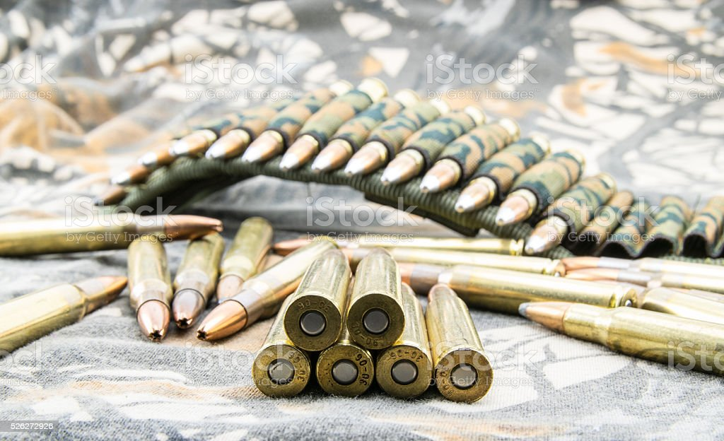 Ammunitions for rifle on camouflage background. stock photo