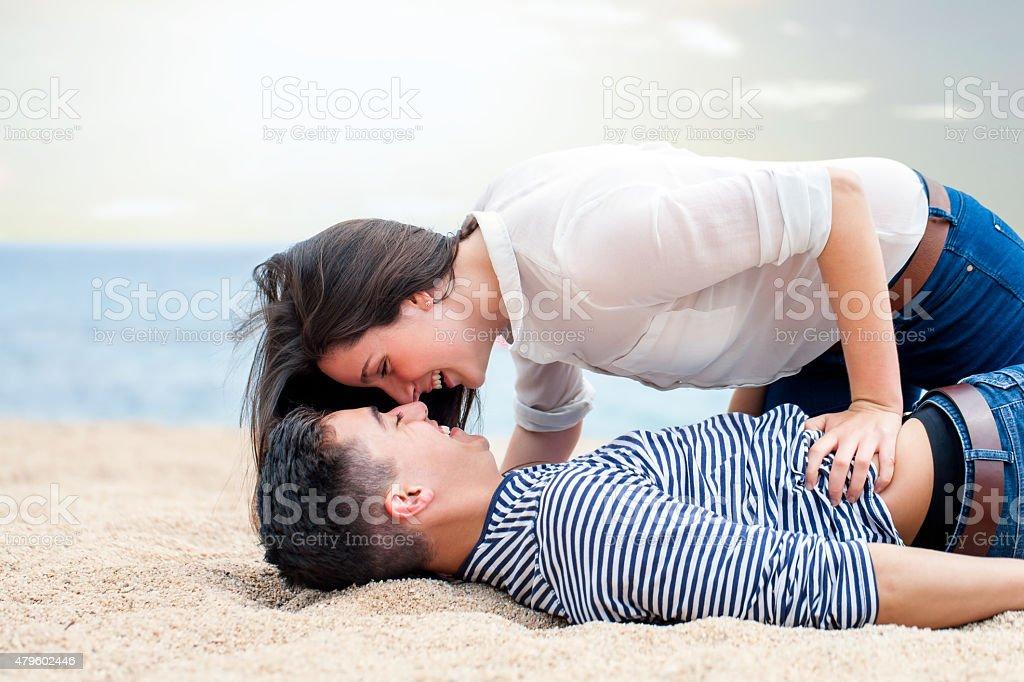 Amorous teen couple on beach. stock photo