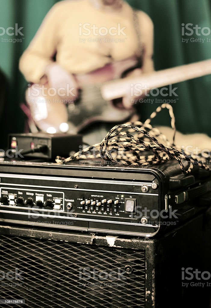 Amplifier and Man Playing Guitar in Background stock photo