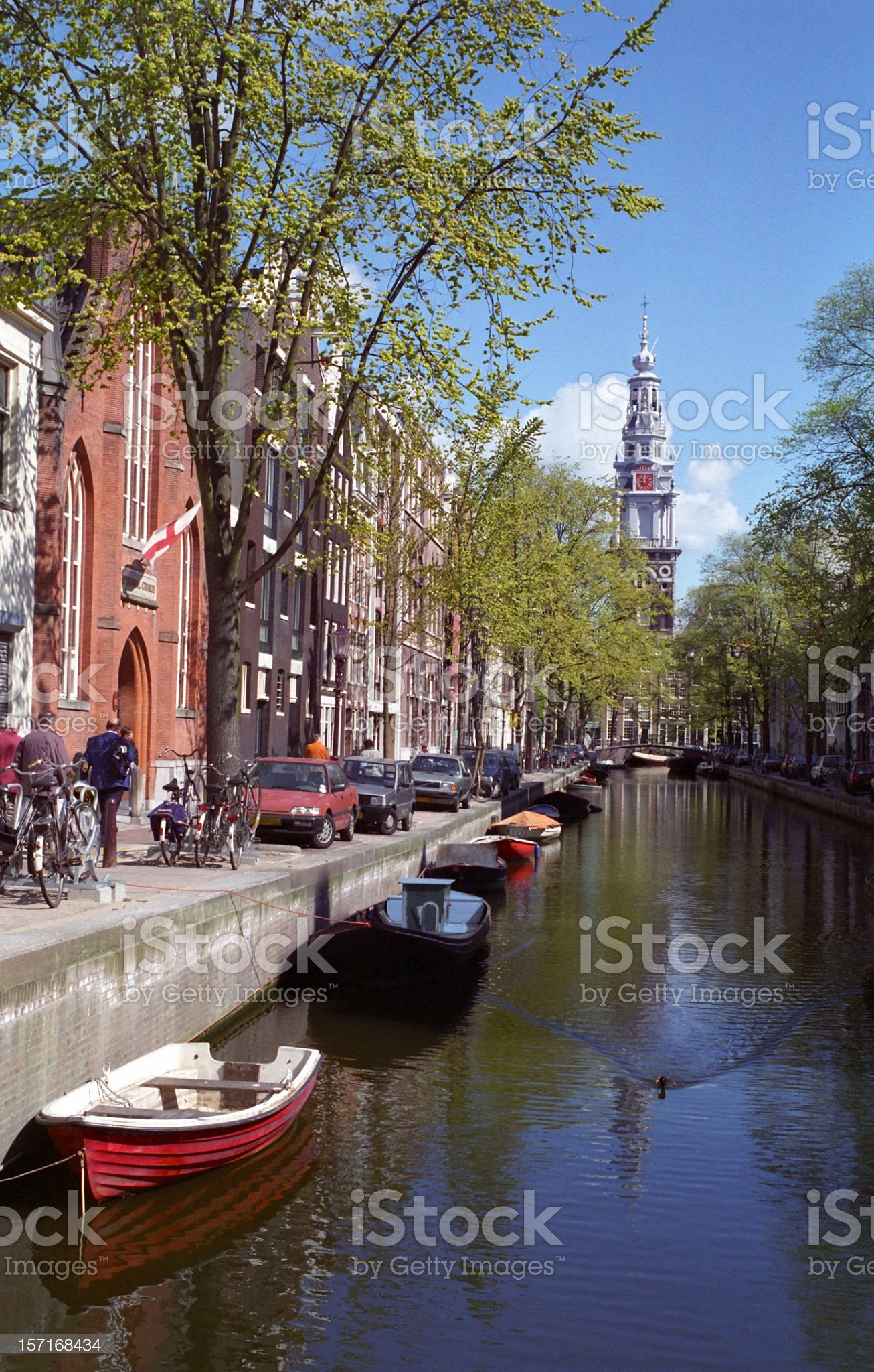Amsterdam canal with boats on the water and people walking royalty-free stock photo