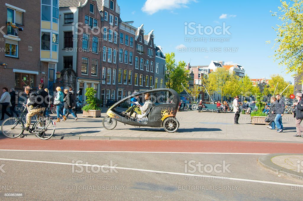 Amsterdam downtown, bicycle taxi cyclist waits for clients, the Netherlands. stock photo