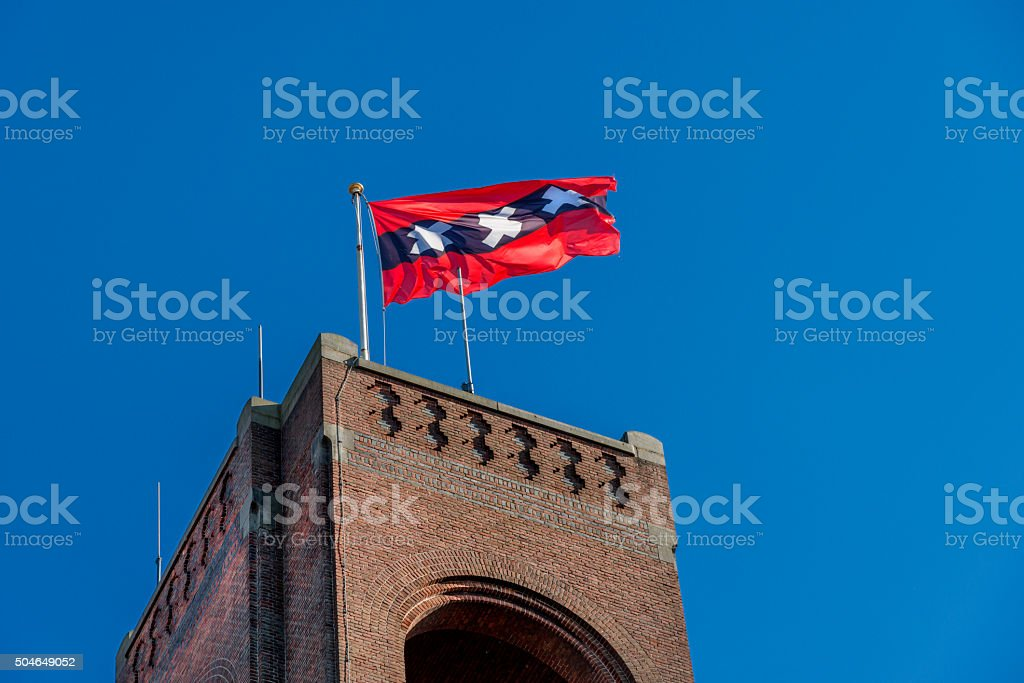 Amsterdam flag on Brick stone tower of Amsterdam stock market. stock photo