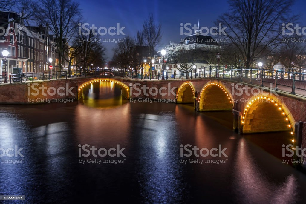 Amsterdam night scene with its canals and bridges reflection on the calm water, Netherlands stock photo