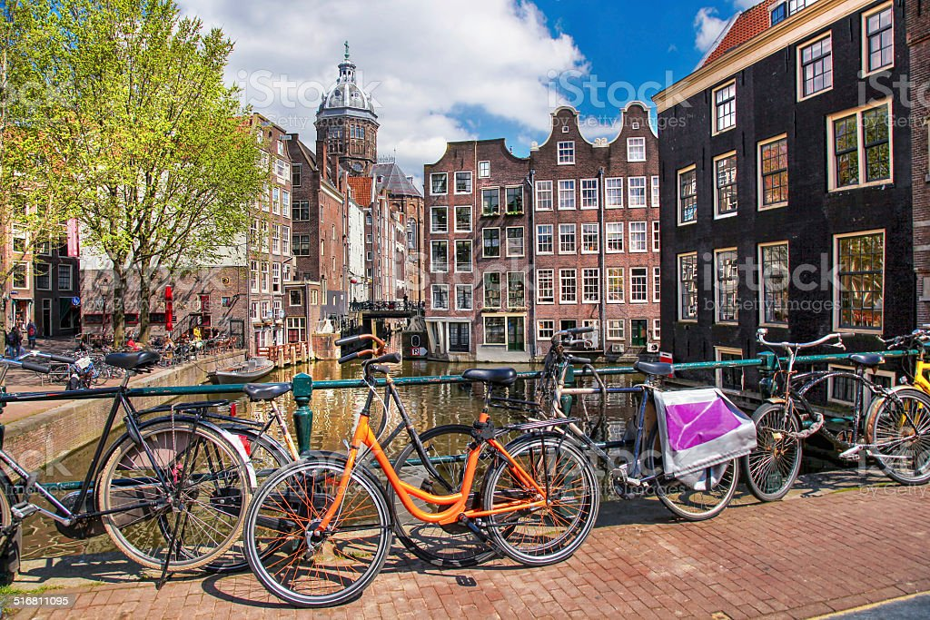 Amsterdam with bicycles against boats on canal in downtown, Holland stock photo