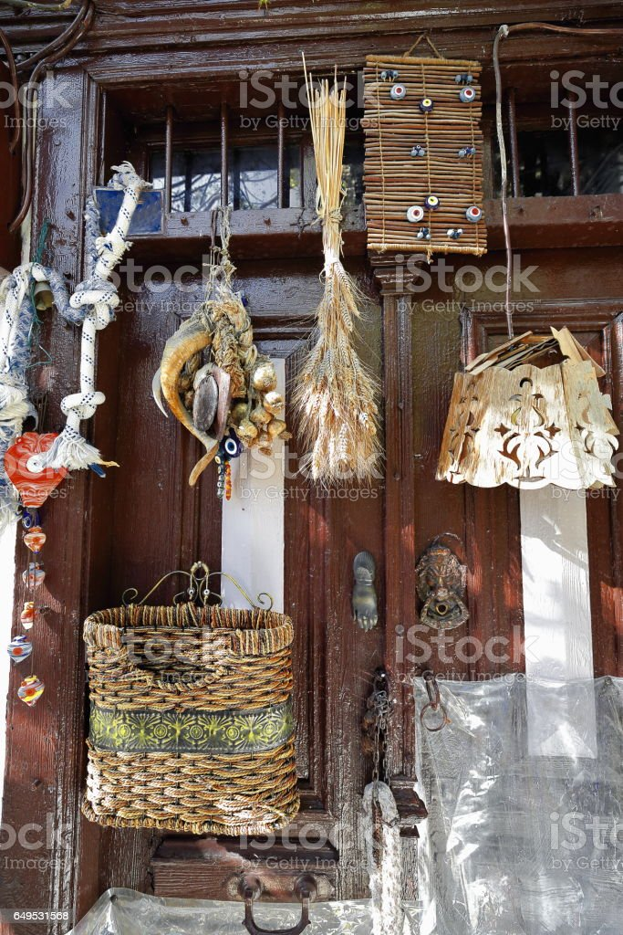 Amulets and wicker-wood-straw items hanging on old door. Kas-Turkey. 1784 stock photo