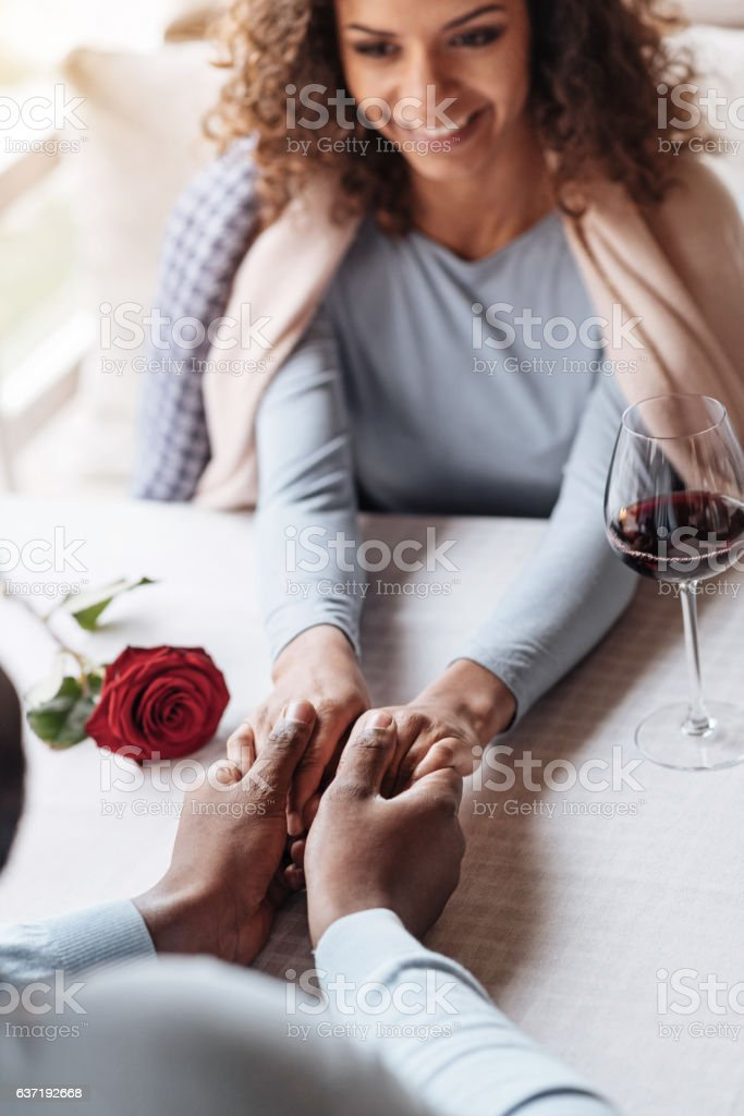 Amused African American couple holding hands in the restaurant stock photo