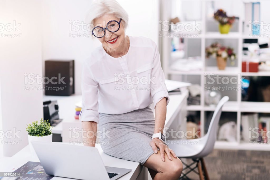 Amused funny business lady using the device in the office stock photo