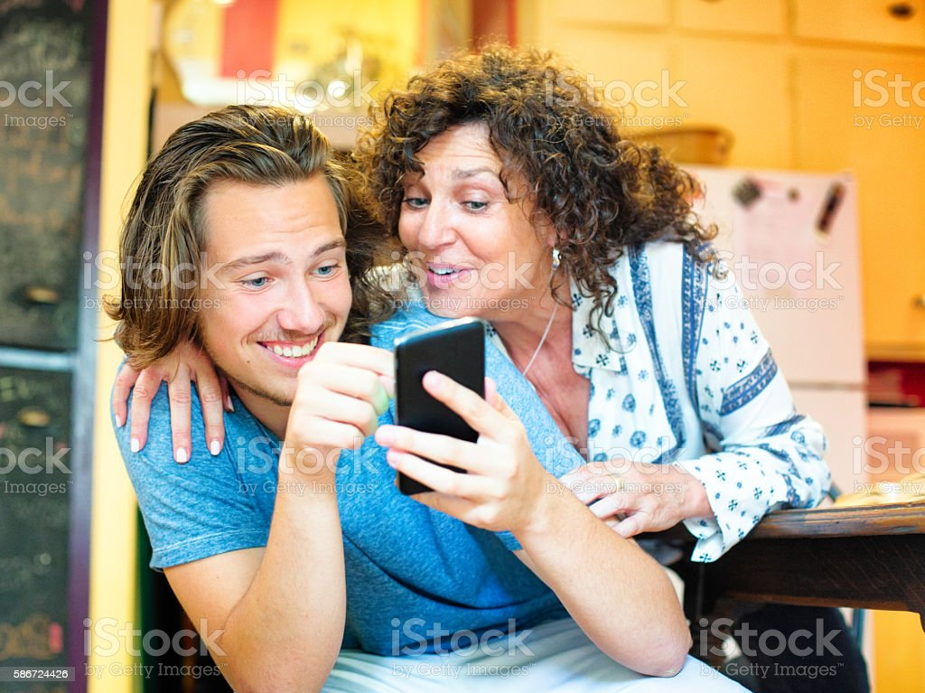 Amused male teenager shows mobile phone game to delighted mother stock photo