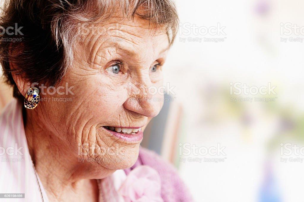Amused old lady watches something smiling, eyes twinkling, eyebrows raised stock photo