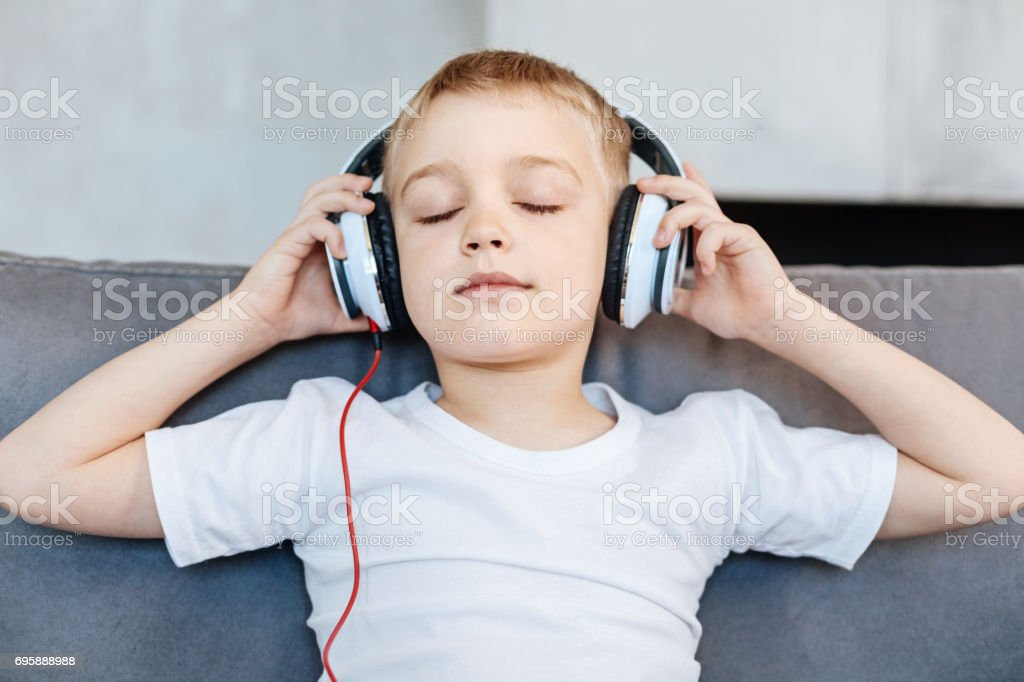 Amusing charismatic boy listening to some music stock photo