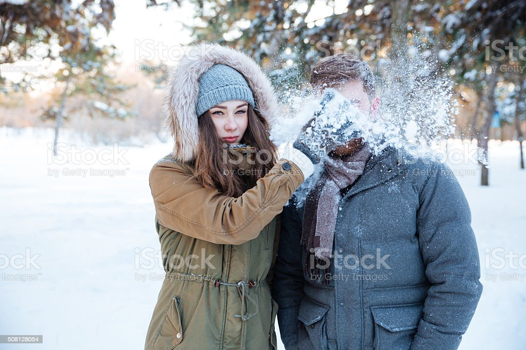 Amusing woman thowing snowball in her boyfriend face stock photo