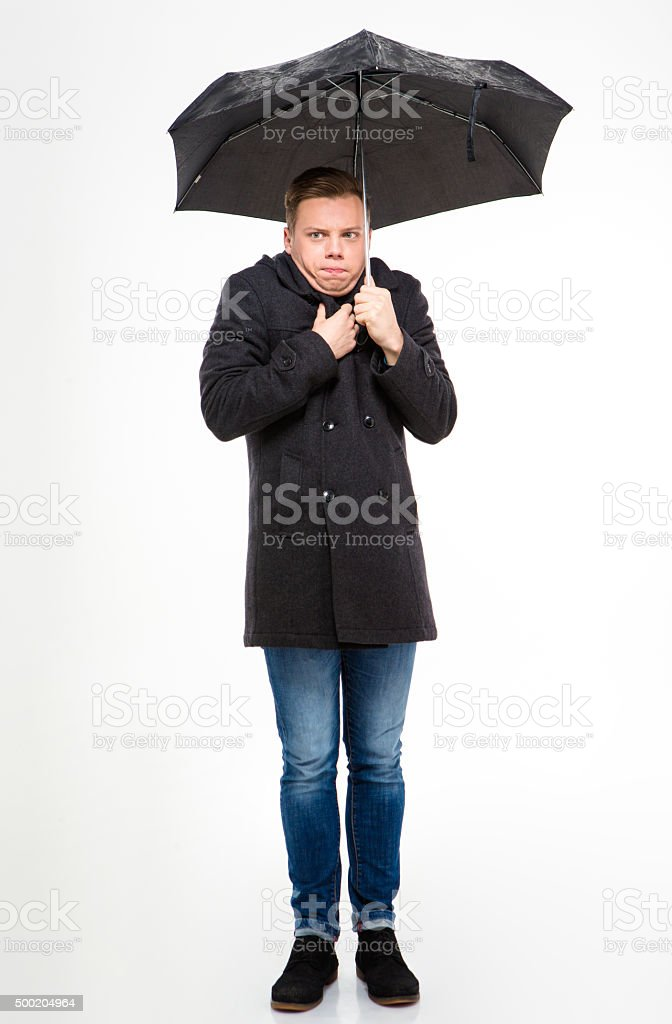 Amusing young man standing and feeling cold under umbrella stock photo