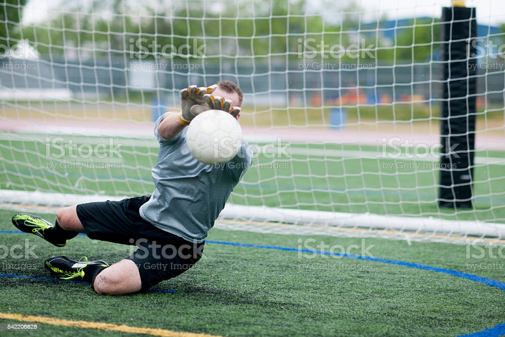 An action shot of goalie catching a soccer ball mid stock photo