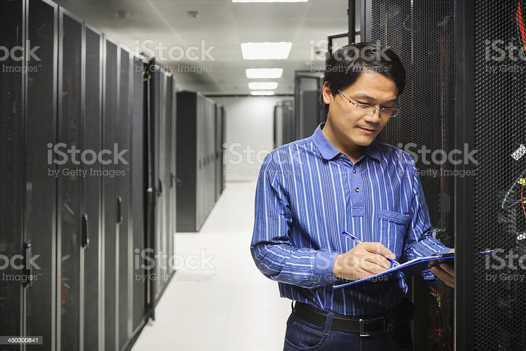 An administrator working on a server in a hallway royalty-free stock photo