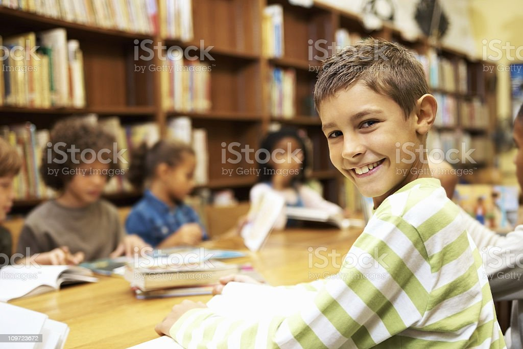 An adorable student reading book while sitting in school library royalty-free stock photo