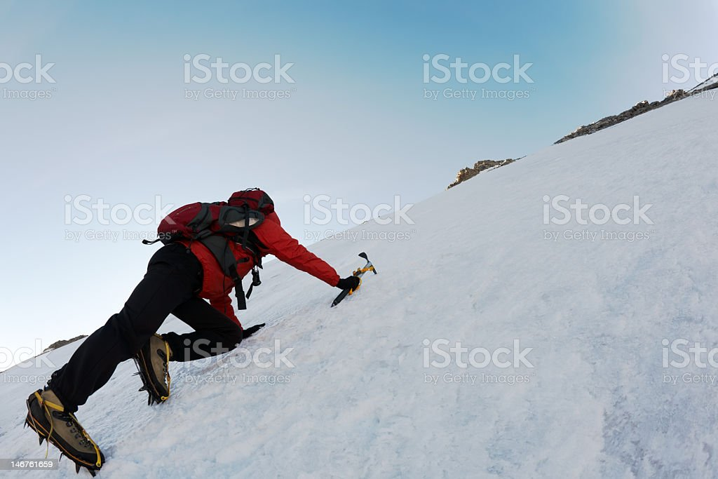 An adult explorer ice climbing with a pick and ice shoes stock photo