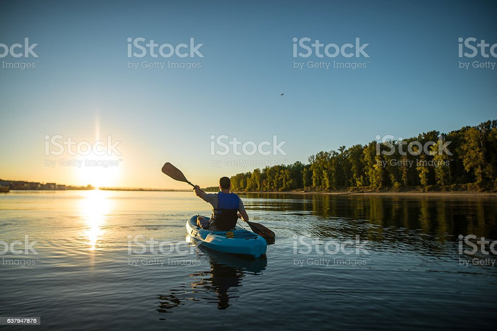 An adult male is kayaking at sunset on a peaceful stock photo