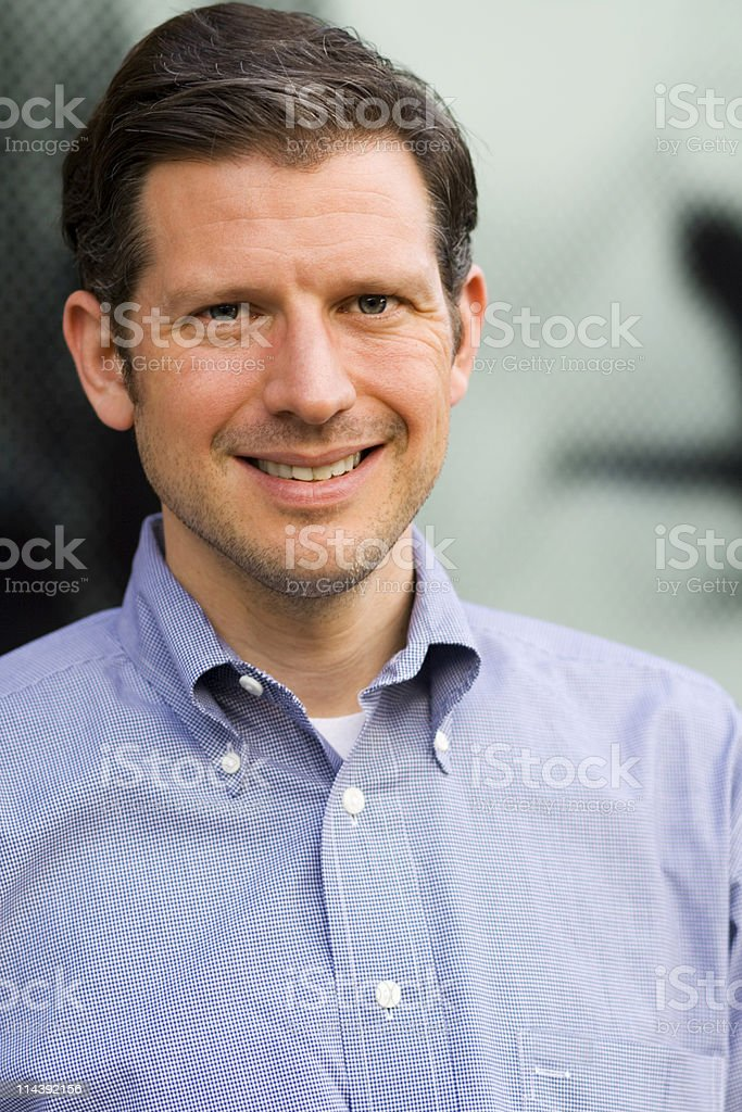 An adult man smiling and wearing a blue collared shirt royalty-free stock photo