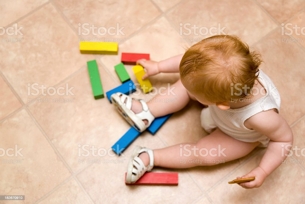 An aerial photograph of a baby playing with colored blocks stock photo