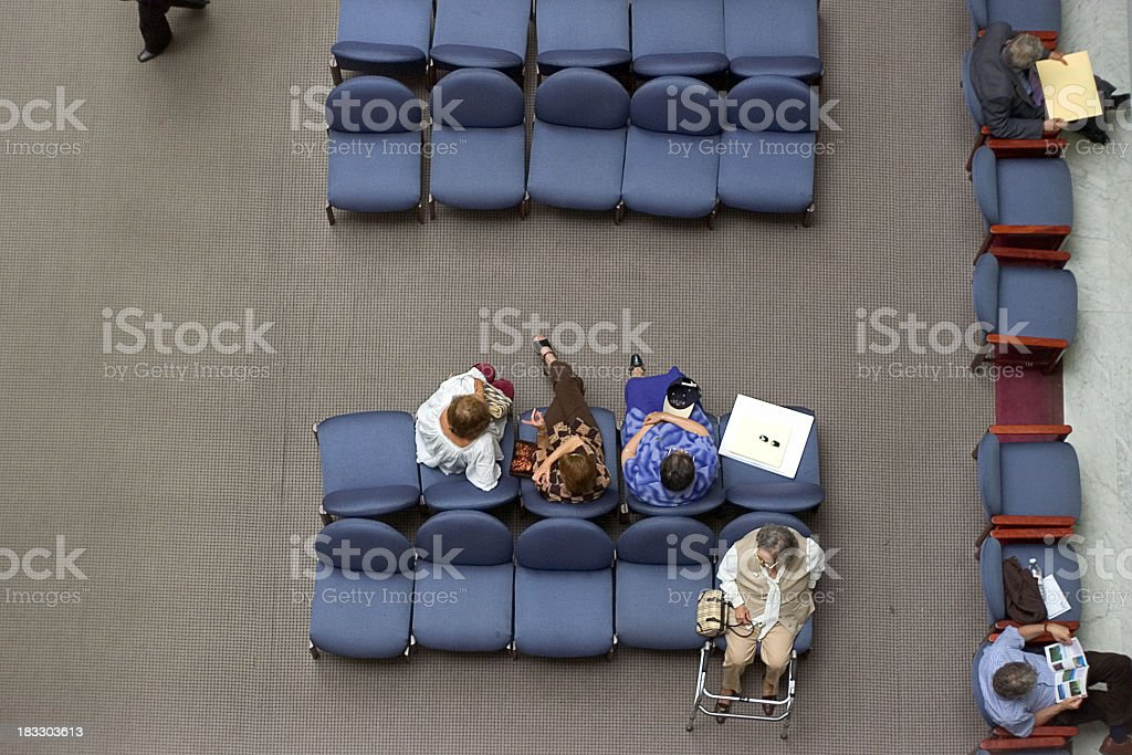 An aerial shot of people sitting in waiting chairs stock photo