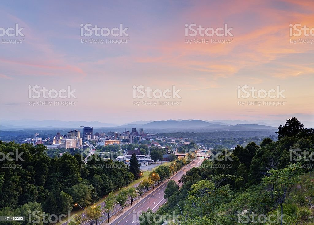 An aerial view of a road and skyline of Asheville at dusk stock photo