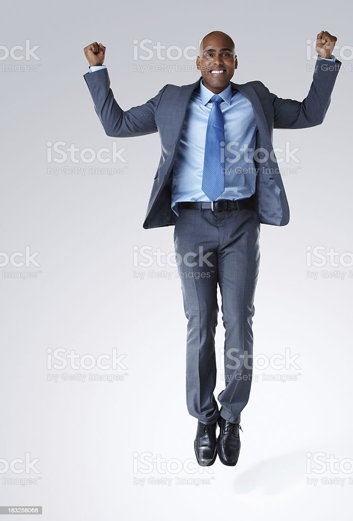 An African American business man jumping against white royalty-free stock photo