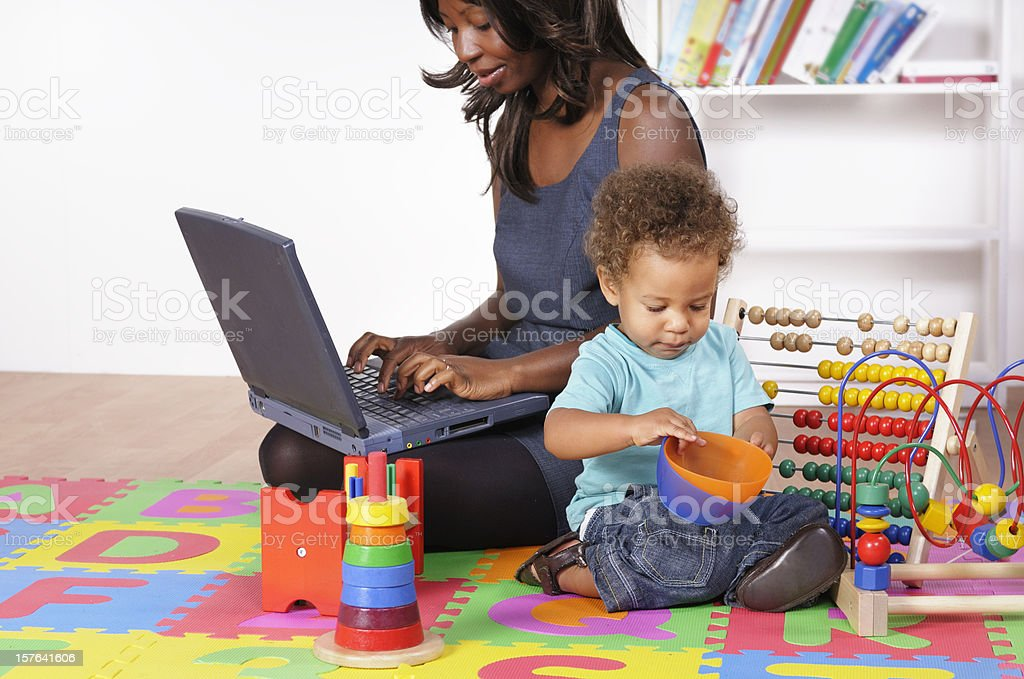 An African American Businesswoman Working While Her Son Plays stock photo