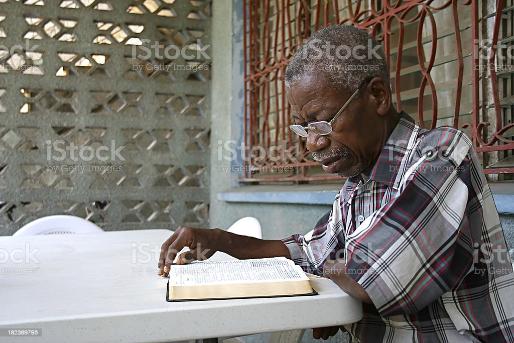 An African elderly gentleman reading a Bible royalty-free stock photo