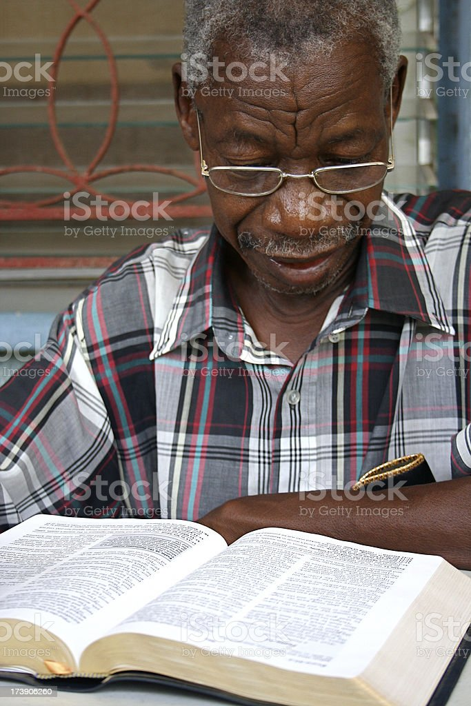 An African senior man reading a bible at a table stock photo