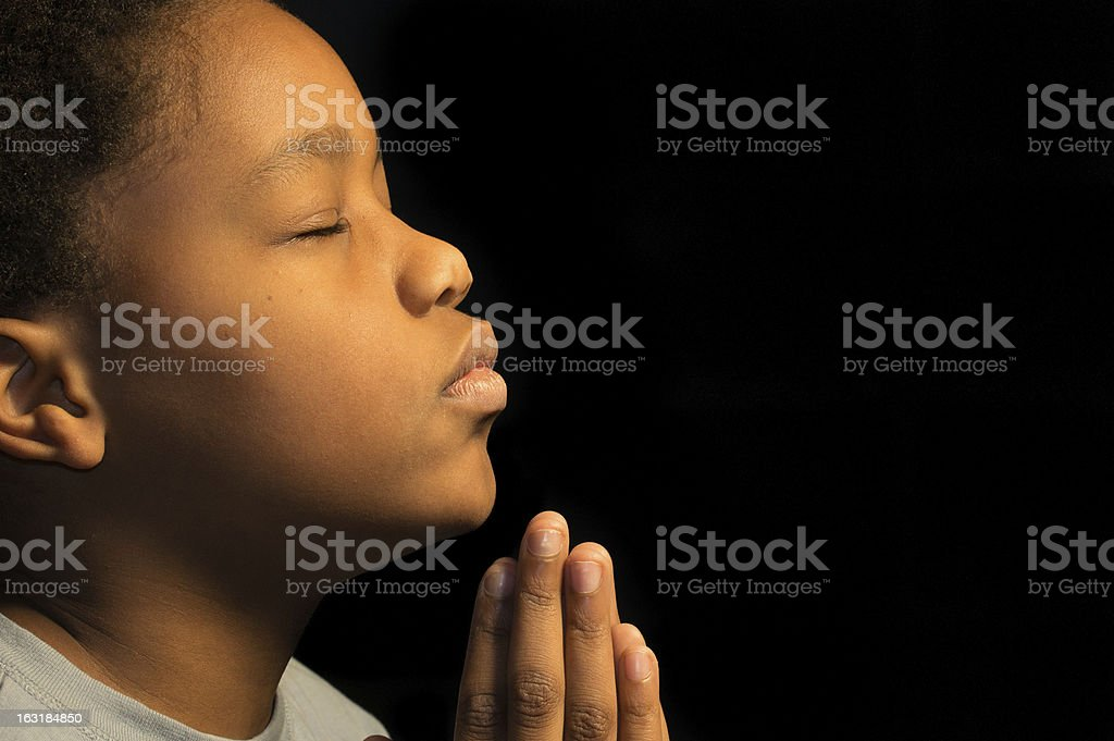 An African-American boy praying to his God stock photo