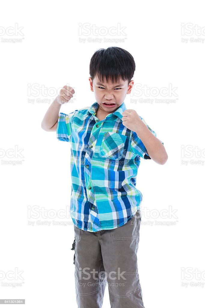 An aggressive asian child. Boy looking furious. Negative expressions stock photo