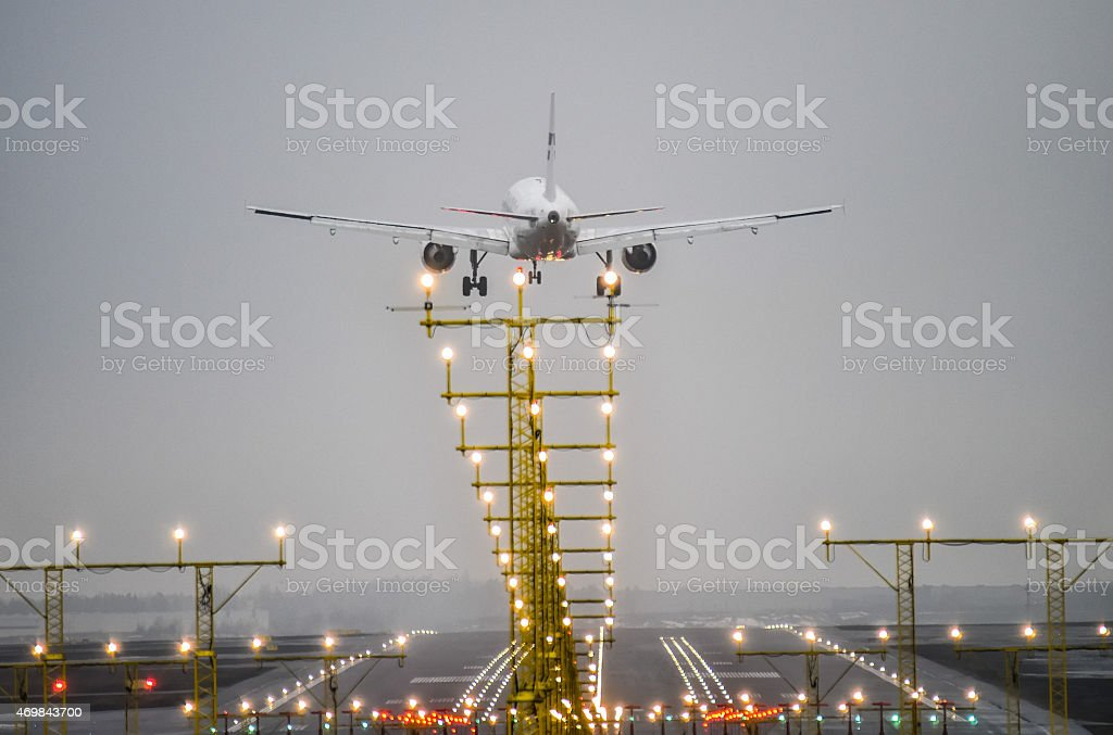 An airplane landing on a runway at a lit up airport stock photo