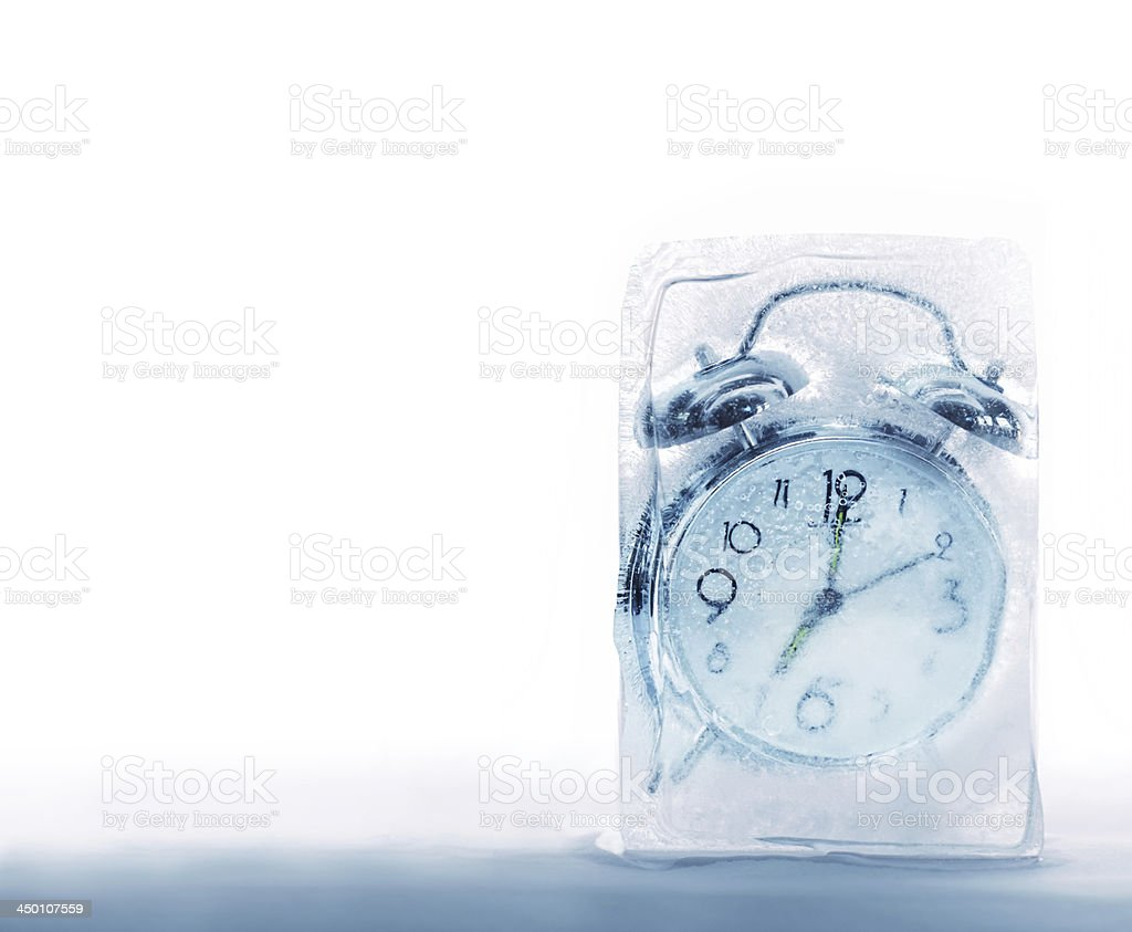 An alarm clock frozen in a block of ice stock photo