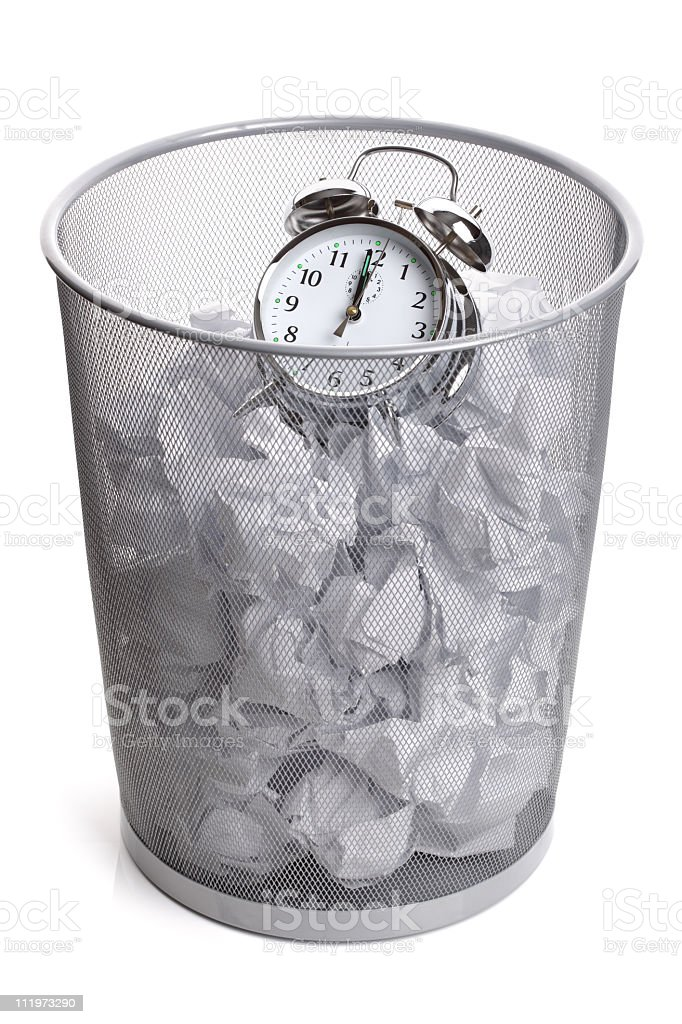 An alarm clock in a filled trash can stock photo