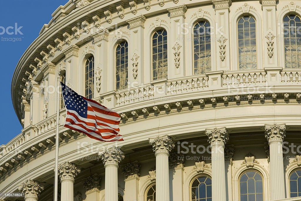 An American flag in front of the U S Capitol Building  stock photo