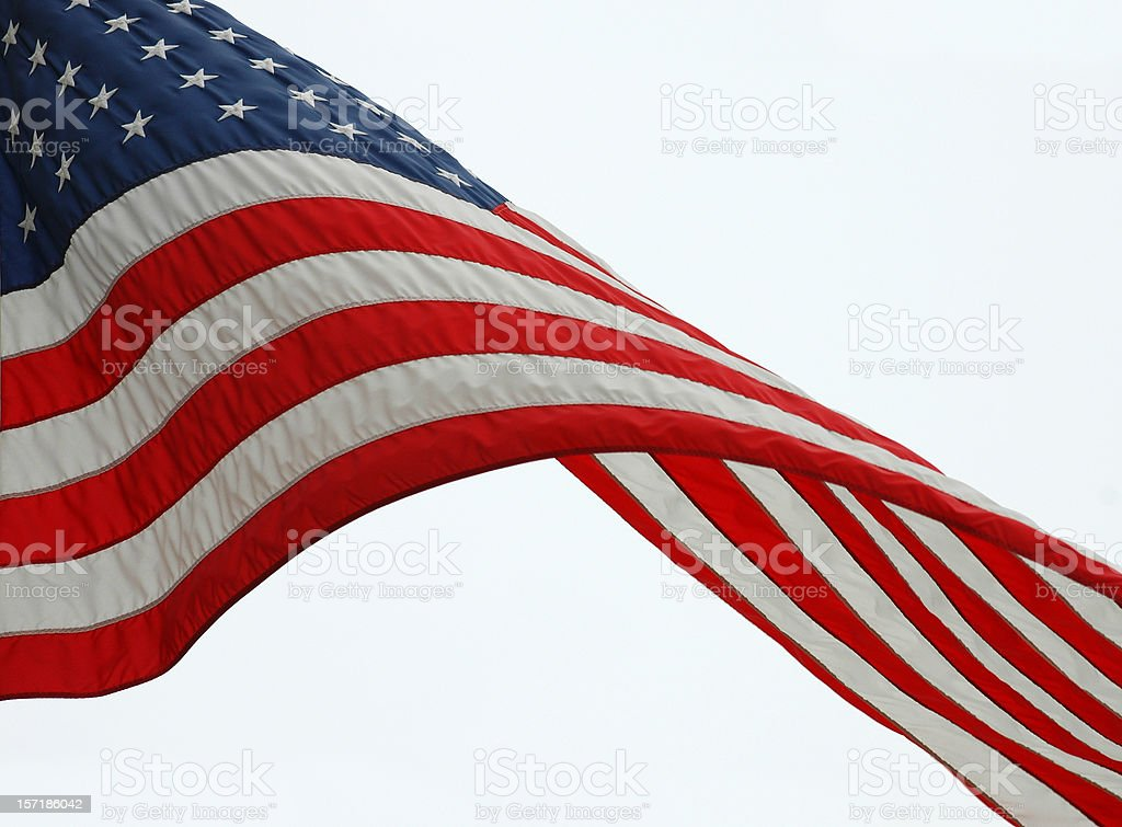 An American Flag waving in the wind in a cloudy day royalty-free stock photo