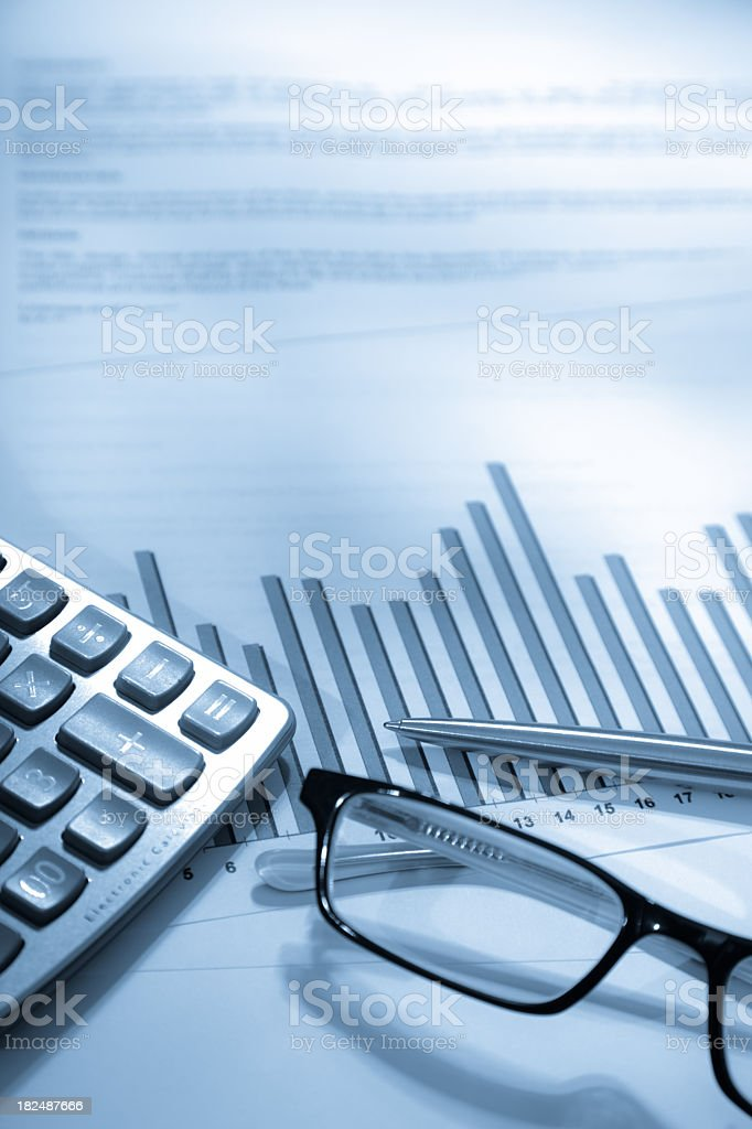 An analytical graph chart and a pair of spectacles stock photo