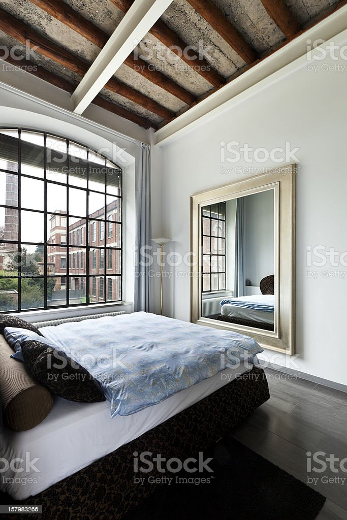 An angled view of a bed, wall mirror, and picture window  stock photo