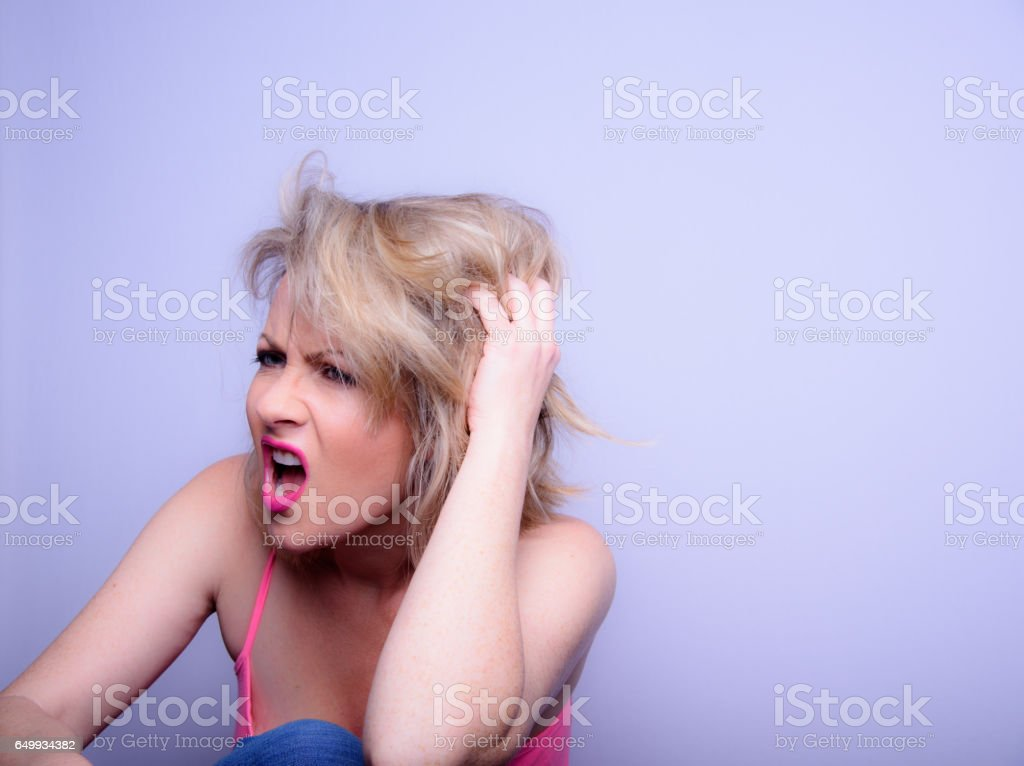 An Angry Blonde Woman Grabbing Her Head stock photo