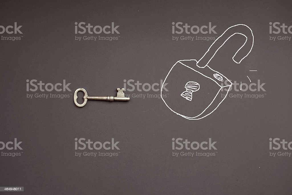 An antique metal key with a chalk drawing of an open lock stock photo