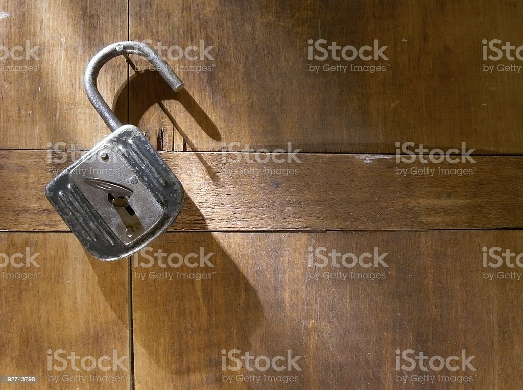 An antique padlock against a wood background stock photo