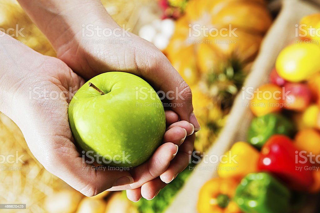 An apple a day: feminine hands holding fruit at market royalty-free stock photo