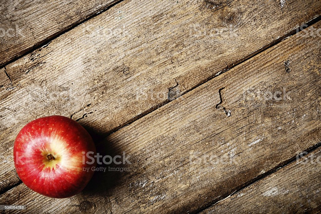 An apple a day. Single fruit on weathered wood stock photo