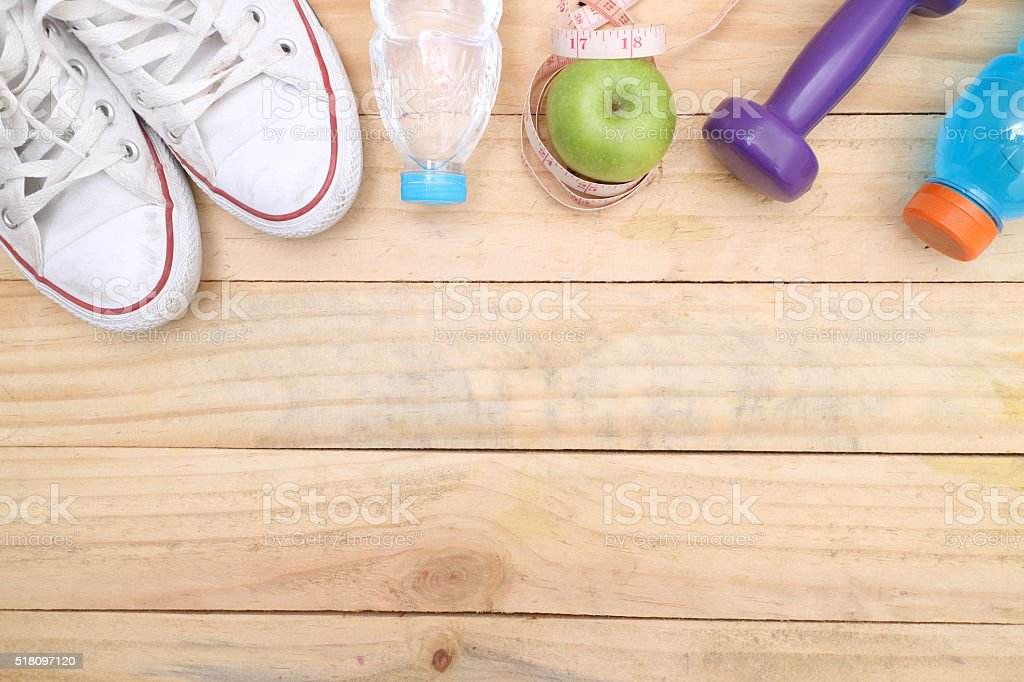 An apple, a measuring tape and dunbbell stock photo