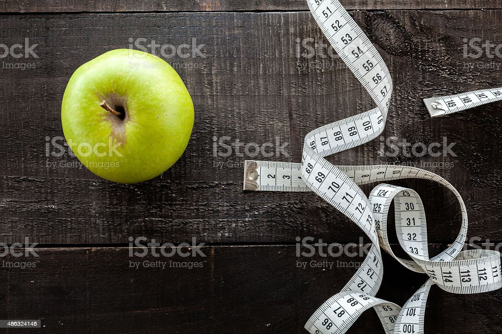 An Apple surrounded by a measuring tape tailor on wood stock photo