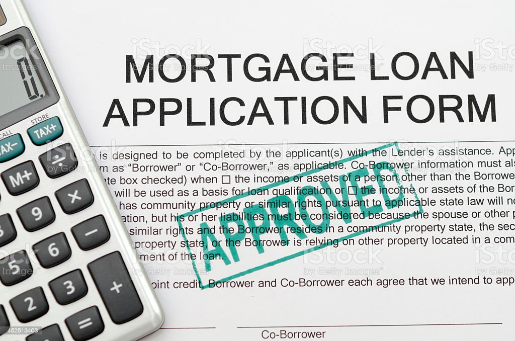 An approved mortgage loan application form with calculator stock photo