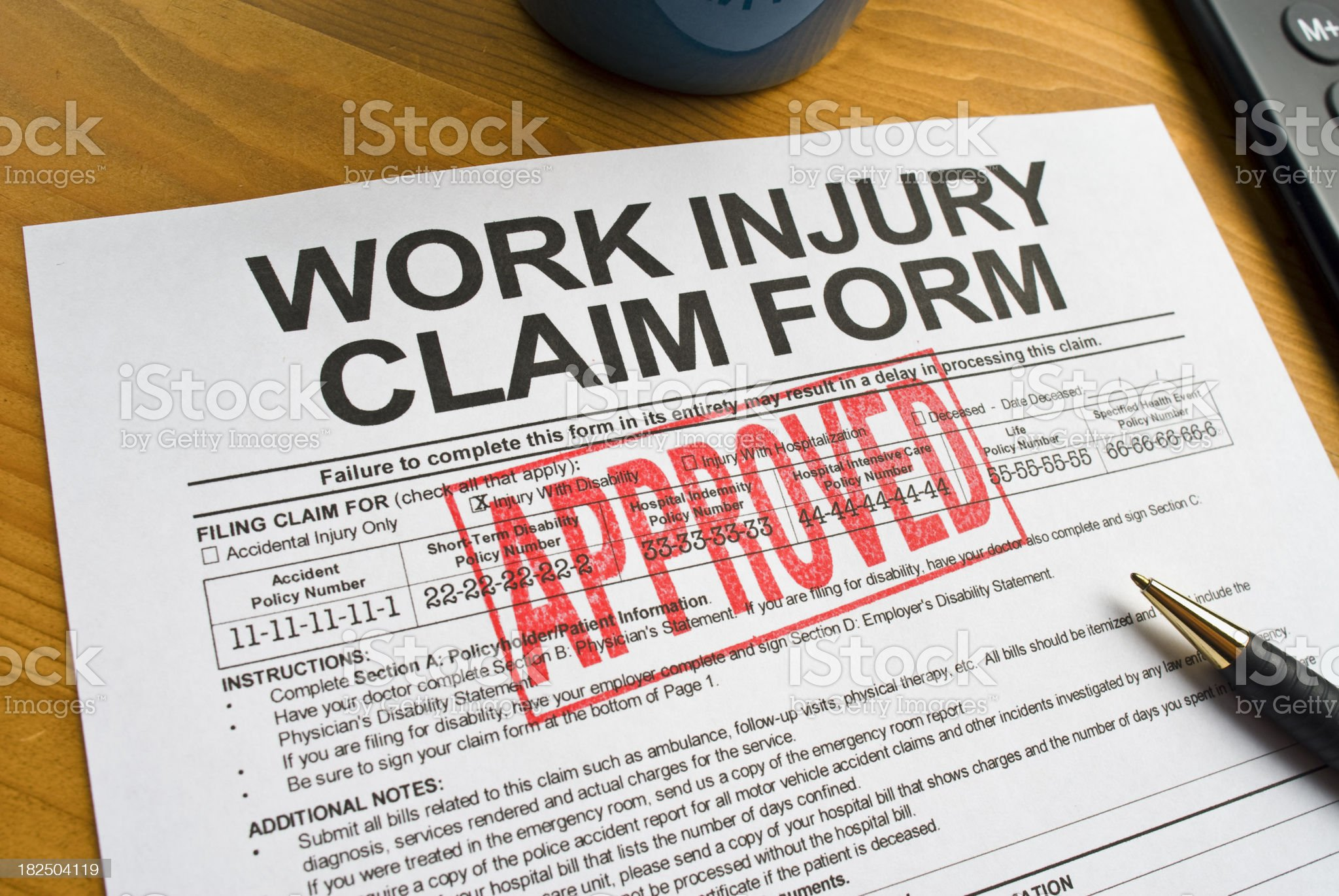 An approved work injury claim form on a desktop royalty-free stock photo