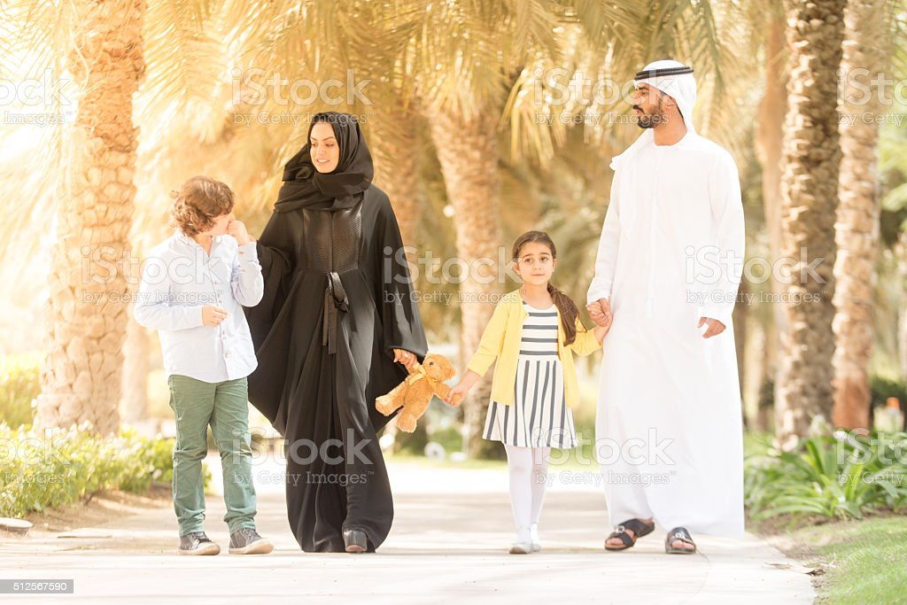 An Arab family with their children walking in the park stock photo