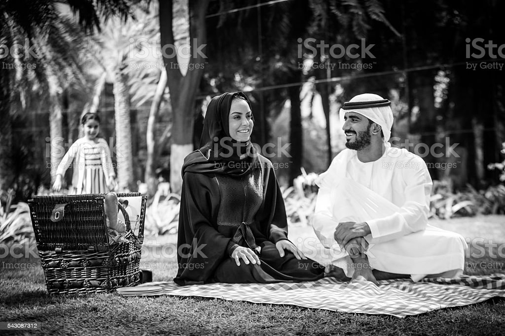 An Arab family with their daughter in a park stock photo